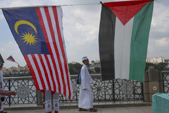 A Muslim walks to Friday prayer as Malaysia and Palestine flags on display in Putrajaya, Malaysia, Friday, Dec. 22, 2017. Malaysia Prime Minister Najib Razak leads huge rally to protest US move to recognize Jerusalem as Israel's capital. (AP Photo/Vincent Thian)
