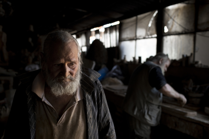 In this Friday, Oct. 13, 2017 photo, pensioner Panayotis Goumas, 74, helps his brother Haralambos in his sculpture and ceramic workshop, in the Egaleo suburb of Athens. (AP Photo/Petros Giannakouris)