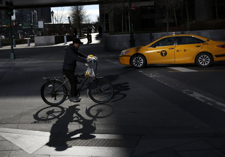 In this Thursday, Dec. 21, 2017 photo, a man making deliveries rides an electronic bike in New York. A plan to intensify a crackdown on electric bicycles is causing concern among the New York City's delivery workforce. (AP Photo/Seth Wenig)