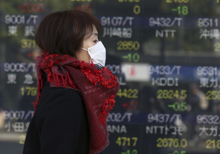 A woman walks by an electronic stock board of a securities firm in Tokyo, Monday, Dec. 25, 2017. Shares were lower in quiet trading Monday in the few Asian markets open during the Christmas holiday. (AP Photo/Koji Sasahara)