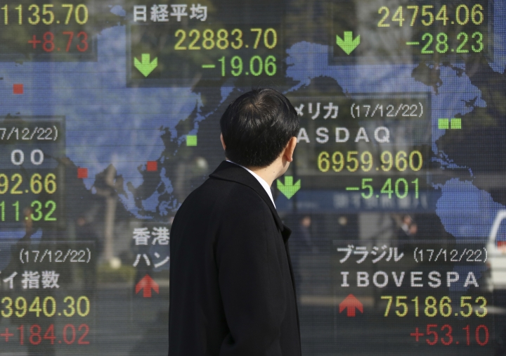 A man looks at an electronic stock board of a securities firm in Tokyo, Monday, Dec. 25, 2017. Shares were lower in quiet trading Monday in the few Asian markets open during the Christmas holiday. (AP Photo/Koji Sasahara)