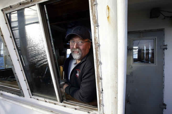 """In this Wednesday, Dec. 6, 2017 photo scallop fisherman Eric Hansen, of Marion, Mass., stands for a photo aboard his fishing vessel """"Endeavor,"""" in Fairhaven, Mass. Fishermen in the nation's most lucrative port are turning a wary eye toward an emerging upstart: the offshore wind industry. New Bedford fishermen say they're concerned about navigating a forest of turbines to get to their historical fishing grounds and getting trawling gear caught up on transmission cables on the seafloor. (AP Photo/Steven Senne)"""