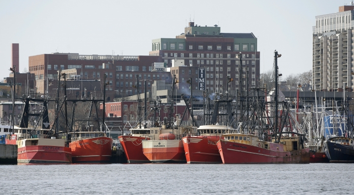In this Wednesday, Dec. 6, 2017 photo fishing vessels are docked in New Bedford Harbor, in New Bedford, Mass. Fishermen in the nation's most lucrative port are turning a wary eye toward an emerging upstart: the offshore wind industry. New Bedford fishermen say they're concerned about navigating a forest of turbines to get to their historical fishing grounds and getting trawling gear caught up on transmission cables on the seafloor. (AP Photo/Steven Senne)