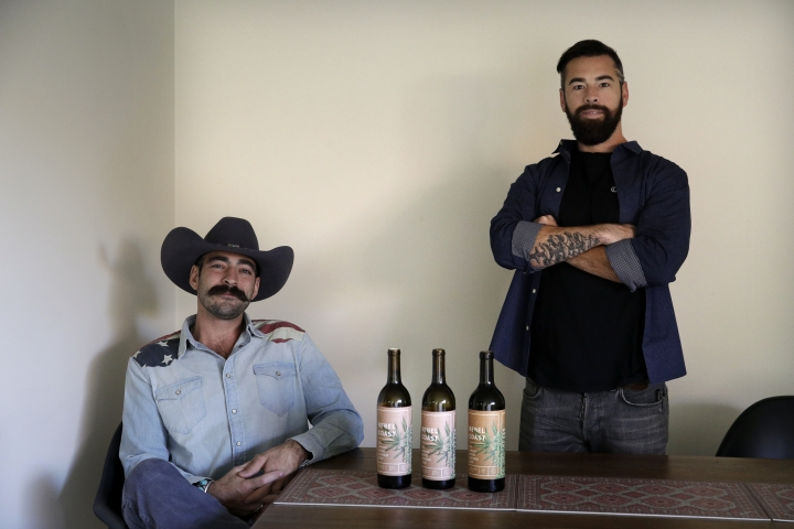 In this Friday, Dec. 22, 2017, photo, Alex Howe, right, and Chip Forsythe, co-founders of Rebel Coast, pause for photos with their cannabis-infused wine in Los Angeles. As the world's largest legal recreational marijuana market takes off in California, the trendsetting state is set to ignite the cannabis-culinary scene. (AP Photo/Jae C. Hong)