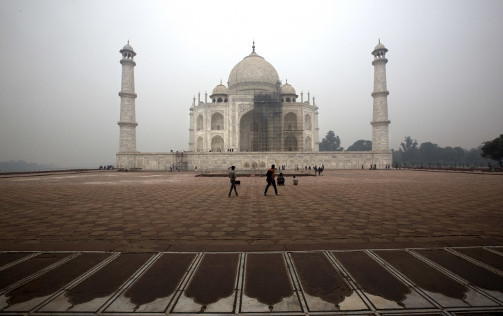 FILE - In this Dec. 5, 2017, file photo, tourists walk around Taj Mahal as workers clean the monument in Agra, India. The travel guidebook publisher Fodor's has published a list of where not to go in 2018 that includes the Taj Mahal. (AP Photo/Manish Swarup, File)