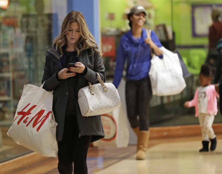 FILE - In this Thursday, Dec. 21, 2017, file photo, customers carry bags as they shop for the holidays at Concord Mills mall in Concord, N.C. Americans were a bit less confident in December than they were in November, but their spirits remained high during the holiday shopping season, according to information released Wednesday, Dec. 27, by the Conference Board. (AP Photo/Chuck Burton, File)