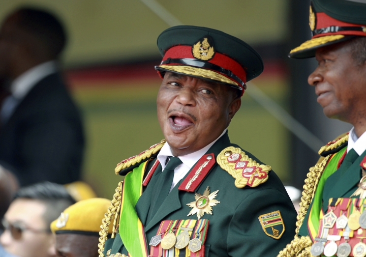 FILE - In this Friday, Nov. 24, 2017 file photo, Army General Constantino Chiwenga smiles during the presidential inauguration ceremony in the capital Harare, Zimbabwe. Zimbabwe's state-run media is reporting that new President Emmerson Mnangagwa has appointed the country's former military commander as one of his two vice presidents. The naming of Constantino Chiwenga deepens concerns among some in the southern African nation about the military's close ties with Mnangagwa, who took power last month after Chiwenga led a military takeover to oust longtime leader Robert Mugabe. (AP Photo/Tsvangirayi Mukwazhi, File)