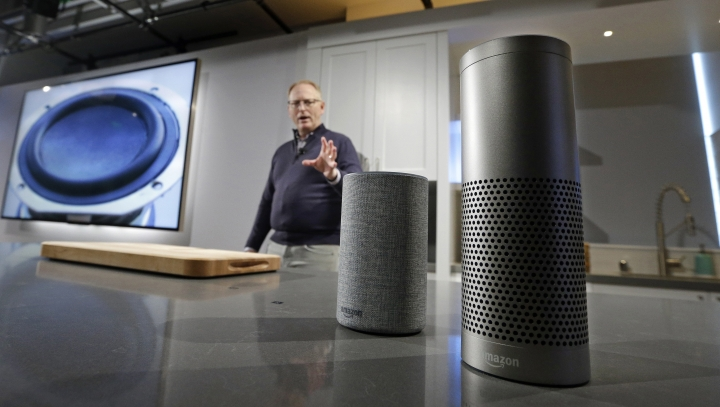 FILE - In this Wednesday, Sept. 27, 2017, file photo, David Limp, senior vice president of Devices and Services at Amazon, displays a new Echo, left, and an Echo Plus during an event announcing several new Amazon products by the company, in Seattle. Internet-connected lights, locks and laundry machines are on the cusp of broadening beyond tech-savvy enthusiasts. Voice-activated speakers such as Amazon's Echo and Google Home are partly the reason. The more people use such speakers, the more they seek out what else they can do. (AP Photo/Elaine Thompson, File)