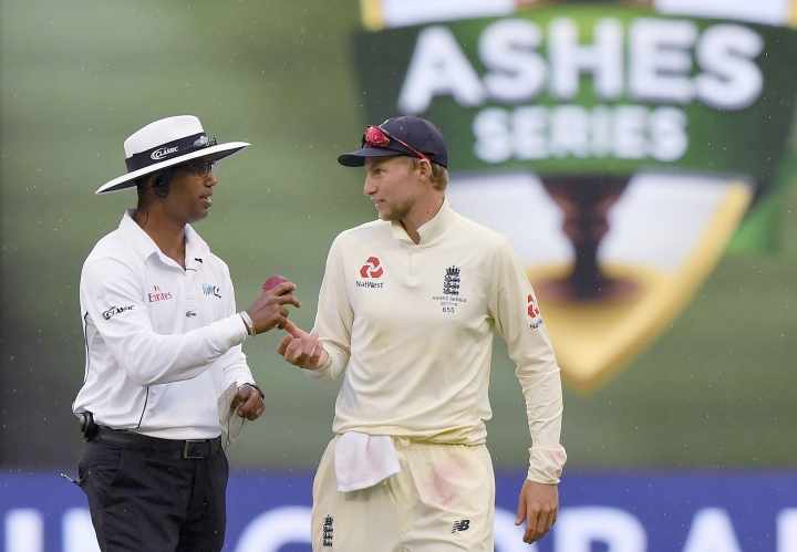 England's Joe Root, right, talks with umpire Kumar Dharmasena as rain interrupts play during the fourth day of their Ashes cricket test match against Australia in Melbourne, Australia, Friday, Dec. 29, 2017. (AP Photo/Andy Brownbill)