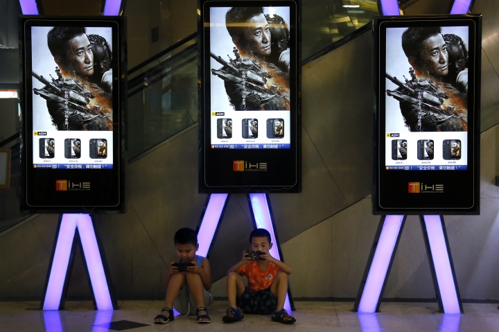 "FILE - In this Aug. 10, 2017, file photo, children use smartphones near monitors displaying Chinese action movie ""Wolf Warrior 2"" at a cinema in Beijing. China's total domestic movie ticket sales rose 13.5 percent in 2017 to 55.9 billion yuan ($8.6 billion), a state news agency said Monday, Jan. 1, 2018. The top-grossing title was the mainland-made action picture ""Wolf Warrior 2,"" which took in 5.7 billion yuan ($875 million), the Xinhua News Agency said, citing data from the State Administration of Press, Publication, Radio, Film and Television. (AP Photo/Andy Wong, File)"