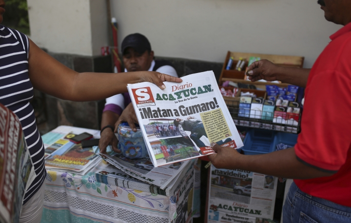 """FILE - In this Dec. 20, 2017 file photo, a man buys a newspaper carrying the Spanish headline """"They killed Gumaro!"""" on the sidewalk in Acayucan, Veracruz state, Mexico. For some, Gumaro Perez was an experienced reporter who earned the nickname """"the red man"""" for his coverage of bloody crimes in Acayucan, Veracruz, but in the eyes of prosecutors he was an alleged drug cartel operative who met a grisly end when he was shot dead Dec. 19. (AP Photo/Felix Marquez, File)"""