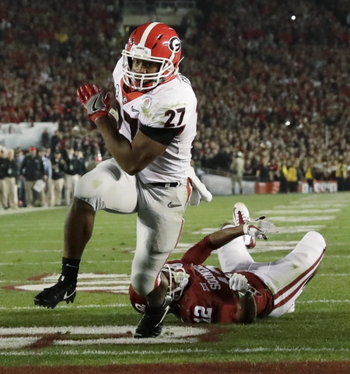 Georgia running back Nick Chubb (27) gets past Oklahoma defensive back Will Johnson (12) to run for a touchdown late in the second half of the Rose Bowl NCAA college football game, Monday, Jan. 1, 2018, in Pasadena, Calif. (AP Photo/Gregory Bull)