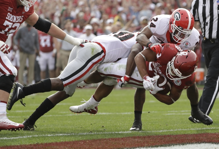 Oklahoma running back Rodney Anderson dives for a touchdown between Georgia defensive back J.R. Reed, left, and safety Dominick Sanders, right, during the first half of the Rose Bowl NCAA college football game, Monday, Jan. 1, 2018, in Pasadena, Calif. (AP Photo/Gregory Bull)