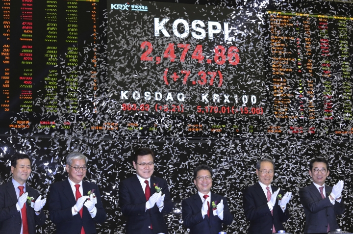Choi Jong-ku, third from left, chairman of the Financial Services Commission, applauds with other participants during the opening of this year's trading at the Korea Exchange in Seoul, South Korea, Tuesday, Jan. 2, 2018. (AP Photo/Ahn Young-joon)