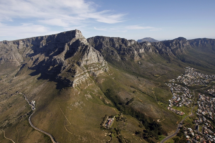 FILE- In this Monday, Oct. 19, 2009 file photo, an aerial view of Table mountain, left, that form's the back drop of Cape Town city, in Cape Town, South Africa. In a dramatic overnight operation, emergency responders have descended on ropes from a cable car on South Africa's Table Mountain to recover the bodies of two male climbers, including a Japanese citizen, who died after falling from a cliff, it was reported Tuesday, Jan. 2, 2018. (AP Photo/Schalk van Zuydam, File)