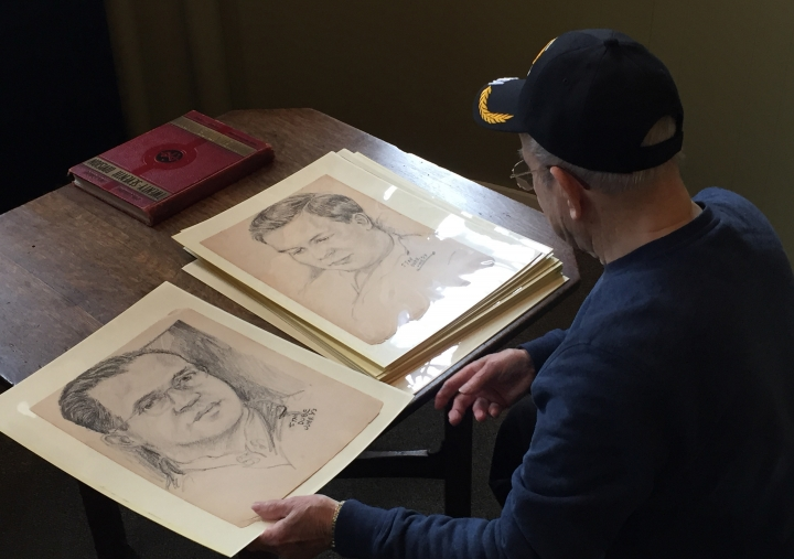 "In this Dec. 8, 2017 photo, World War II veteran Wilfred ""Spike"" Mailloux looks through a series of sketches of U.S. Army 27th Infantry Division soldiers while visiting the New York State Military Museum and Veterans Research Center in Saratoga Springs, N.Y. They were done in Hawaii by Stan Dube in 1943, a year before the 27th Division fought in the Battle of Saipan. Now his son, Ira Dube, is hoping to identify the men, so he has donated his late father's 15 sketches to the museum. (AP Photo/Chris Carola)"