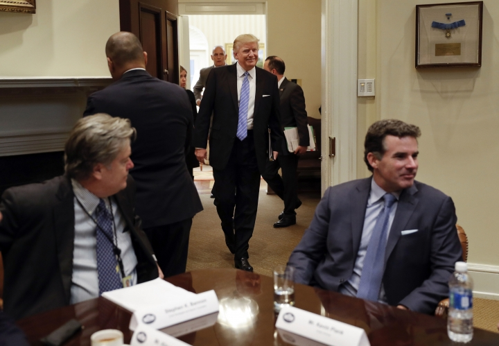 "FILE - In this Jan. 23, 2017, file photo, President Donald Trump smiles as he walks in from the Oval Office of the White House in Washington, to host breakfast with business leaders in the Roosevelt Room. Sitting at the table are then-White House senior adviser Steve Bannon, left, and Kevin Plank, founder, CEO and Chairman of Under Armour. Trump returned fire with both barrels Wednesday against criticism leveled at him in a new book that says he never expected — or wanted — to win the White House, his victory left his wife in tears and a senior adviser thought his son's contact with a Russian lawyer during the campaign was ""treasonous."" (AP Photo/Pablo Martinez Monsivais, File)"