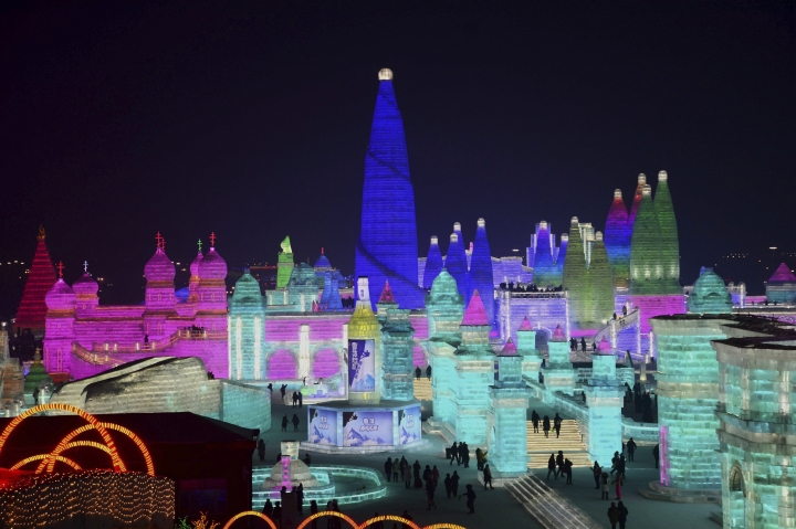 FILE - In this Jan. 2, 2018 file photo, visitors walk among the attractions at the Harbin International Ice and Snow Festival in Harbin in northeastern China's Heilongjiang Province. The Harbin International Ice and Snow Festival is known for massive, elaborate and colorfully lit ice sculptures featuring animals, cartoon characters and famous landmarks. (Chinatopix via AP, File)