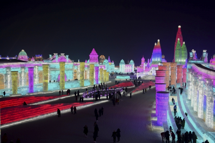 In this Jan. 2, 2018 photo, visitors walk among the attractions at the Harbin International Ice and Snow Festival in Harbin in northeastern China's Heilongjiang Province. The Harbin International Ice and Snow Festival is known for massive, elaborate and colorfully lit ice sculptures featuring animals, cartoon characters and famous landmarks. (Chinatopix via AP)