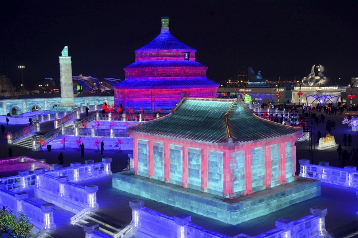 FILE - In this Jan. 2, 2018 photo, visitors walk among the attractions at the Harbin International Ice and Snow Festival in Harbin in northeastern China's Heilongjiang Province. The Harbin International Ice and Snow Festival is known for massive, elaborate and colorfully lit ice sculptures featuring animals, cartoon characters and famous landmarks. (Chinatopix via AP, File)