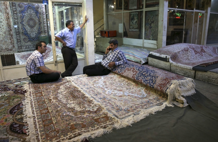 FILE - In this Aug. 10, 2015, file photo, Iranian merchants wait for customers at a carpet market in Tehran's old main bazaar, in Iran. Anger and frustration over the economy has been the main fuel for the surprise eruption of protests that began on Dec. 28, 2017. President Hassan Rouhani, a relative moderate, had promised that the lifting of most international sanctions under Iran's landmark 2015 nuclear deal with the West would revive the long-suffering economy. The end of sanctions did open up a new influx of cash from increased oil exports, but little of that has trickled down to the wider population. At the same time, Rouhani has enforced austerity policies that hit households hard. (AP Photo/Vahid Salemi, File)