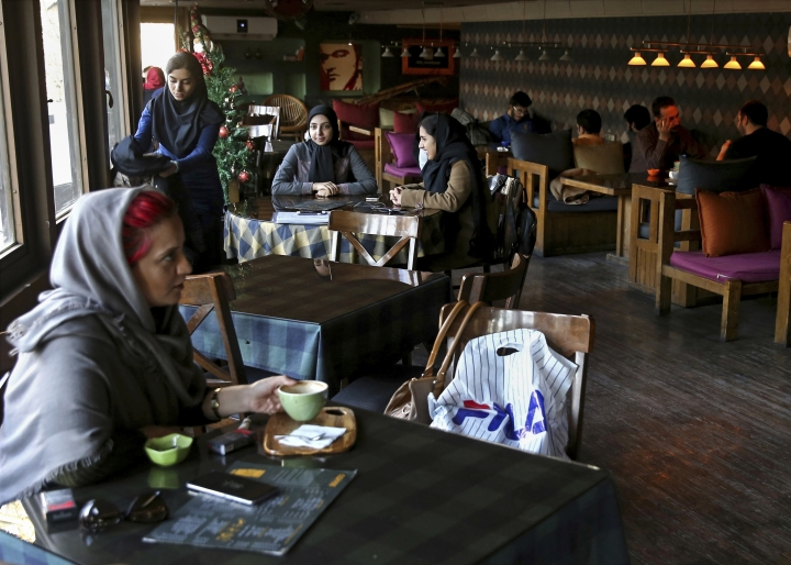 Young people spend their time at a cafe in downtown Tehran, Iran, Wednesday, Jan. 3, 2018. Tens of thousands of Iranians took part in pro-government demonstrations in several cities across the country on Wednesday, Iranian state media reported, a move apparently seeking to calm nerves after a week of protests and unrest that have killed at least 21 people. (AP Photo/Ebrahim Noroozi)