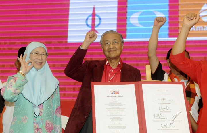 In this Sunday, Jan. 7, 2018, photo, Malaysia former Prime Minister Mahathir Mohamad, center, and Wan Azizah, wife of former Deputy Prime Minister Anwar Ibrahim, wave during a political opposition alliance meeting in Shah Alam, Malaysia. Malaysia's opposition alliance has named 92-year-old former Prime Minister Mahathir Mohamad as its prime minister candidate for upcoming general elections to boost its chances of wrestling power from a coalition that has ruled since independence. (AP Photo/Huey May)