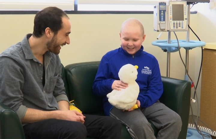 "In this undated photo made from video, 12-year-old cancer patient Ethan Daniels at medical facility in Atlanta speaks with Aaron Horowitz, co-founder and CEO of Sproutel, who designed ""My Special Aflac Duck"" to promote emotional well-being by helping children living with cancer develop a sense of control and manage stress through interactive technology. (AP Photo/Marina Hutchinson)"