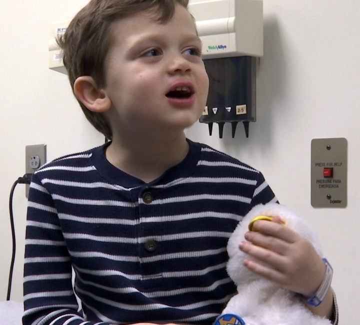 In this undated photo made from video, 5-year-old cancer patient Alex Bridges speaks to a nurse and being comforted by robotic duck just before treatment at medical facility in Atlanta. A plush, robotic duck may soon become a fixture in the world of children who have cancer. The social robot can be silly, happy, angry, scared or sick just like them, and help them cope creatively with their illness through the power of play. (AP Photo/Marina Hutchinson)