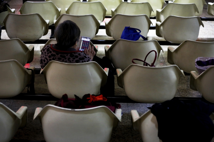 A woman checks stock index through her smartphone at a brokerage house in Beijing, Monday, Jan. 8, 2017. Asian stock markets rose Monday following Wall Street's strong week as traders looked ahead to data releases from China, Japan and the Eurozone. (AP Photo/Andy Wong)