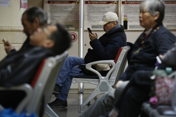 Some investors check stock index through their smartphone at a brokerage house in Beijing, Monday, Jan. 8, 2017. Asian stock markets rose Monday following Wall Street's strong week as traders looked ahead to data releases from China, Japan and the Eurozone. (AP Photo/Andy Wong)