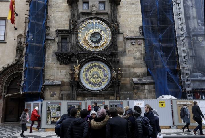 Tourists stand in front of the famed astronomical clock at the Old Town Square in Prague, Czech Republic, Monday, Jan. 8, 2018. Workers stopped the famous medieval astronomical clock on Monday and parts will be taken off site for months for major repairs. Prague officials say the clock installed on the City Hall's tower in 1410 will be completely disassembled and taken for its first comprehensive restoration since World War II. (AP Photo/Petr David Josek)