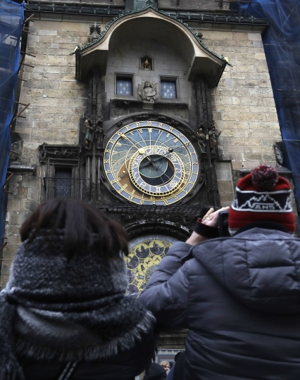 Tourists take a photo of the famed astronomical clock at the Old Town Square in Prague, Czech Republic, Monday, Jan. 8, 2018. Workers stopped the famous medieval astronomical clock on Monday and parts will be taken off site for months for major repairs. Prague officials say the clock installed on the City Hall's tower in 1410 will be completely disassembled and taken for its first comprehensive restoration since World War II. (AP Photo/Petr David Josek)