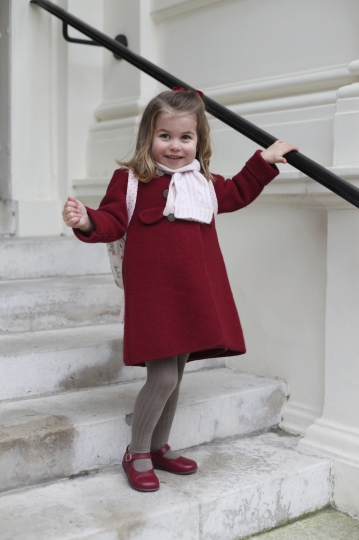 In this handout picture provided by the Duke and Duchess of Cambridge, Britain's Princess Charlotte smiles as she prepares for her first day of nursery at the Willcocks Nursery School, in London, Monday, Jan. 8, 2018. (Duchess of Cambridge via AP)