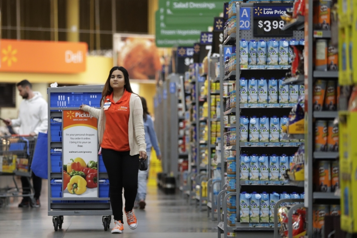 In this Thursday, Nov. 9, 2017, photo, Laila Ummelaila, a personal shopper at the Walmart store in Old Bridge, N.J., pulls a cart with bins as she shops for online shoppers. Personal shoppers collect items on online orders and greet customers at a pickup location in the parking lot. (AP Photo/Julio Cortez)
