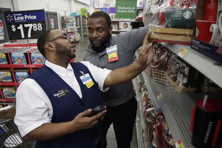 In this Thursday, Nov. 9, 2017, photo, Walmart employee Kenneth White, left, is coached by Shabazz Bonner while using an inventory app during a class at the Walmart Academy at the store in North Bergen, N.J. The retail industry is being radically reshaped by technology and nobody feels that disruption more starkly than the 16 million Americans working as shelf stockers, salespeople and cashiers. (AP Photo/Julio Cortez)