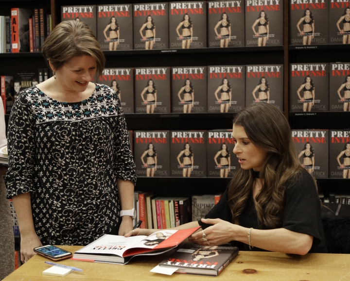 """Danica Patrick, right, autographs her new book for Julie Grunwald during a book signing in Charlotte, N.C., Thursday, Jan. 4, 2018. The transition from race car driver to businesswoman was swift, and Patrick is now adjusting to a new celebrity life that doesn't include driving cars. She hawked her new book all last week, and held her first organized book signing. As for her plans to drive the """"Danica Double"""" and race the Daytona 500 and Indianapolis 500? Well, it's not coming together as quickly as she'd like. (AP Photo/Chuck Burton)"""