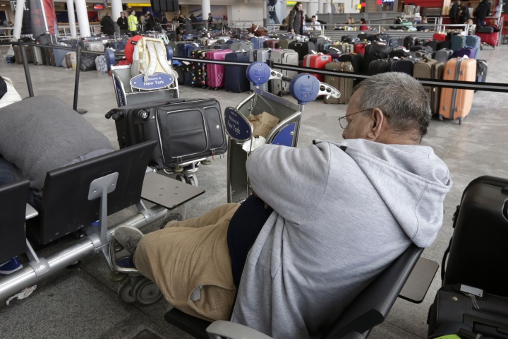"""A passenger rests in the arrivals area of Terminal 4 at New York's John F. Kennedy Airport, near unclaimed luggage, Monday, Jan. 8, 2018. The Port Authority of New York and New Jersey said Monday it will investigate the water pipe break that added to the weather-related delays at Kennedy Airport and will """"hold all responsible parties accountable."""" (AP Photo/Richard Drew)"""