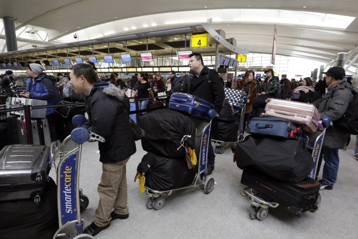 """Passengers at New York's John F. Kennedy Airport Terminal 4 wait for flights, Monday, Jan. 8, 2018. The Port Authority of New York and New Jersey said Monday it will investigate the water pipe break that added to the weather-related delays at Kennedy Airport and will """"hold all responsible parties accountable."""" (AP Photo/Richard Drew)"""