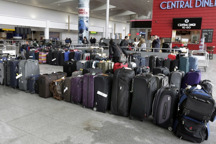 "A woman looks through unclaimed baggage at New York's John F. Kennedy Airport Terminal 4, Monday, Jan. 8, 2018. The Port Authority of New York and New Jersey said Monday it will investigate the water pipe break that added to the weather-related delays at Kennedy Airport and will ""hold all responsible parties accountable."" The agency said there were still some delays on Monday, the day after the pipe break in the privately operated Terminal 4 broke, causing water to flood the terminal and significantly disrupt operations. (AP Photo/Richard Drew)"