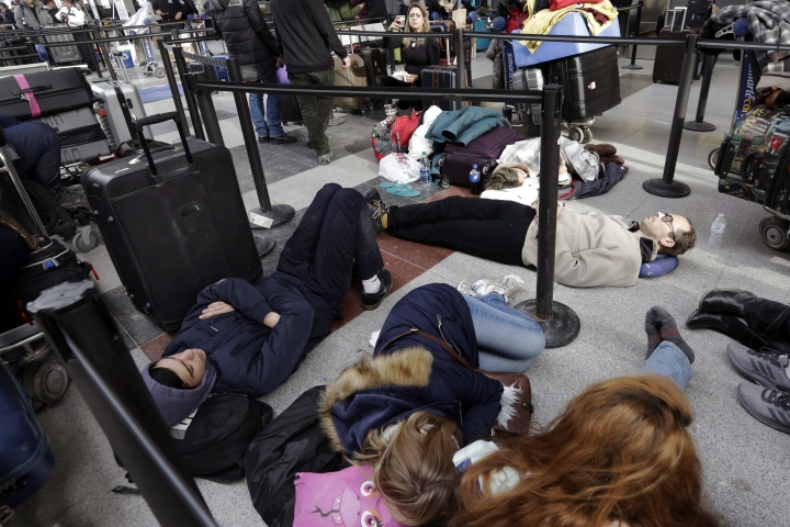 """Avianca passengers lay on the floor while waiting for their flight at New York's John F. Kennedy Airport Terminal 4, Monday, Jan. 8, 2018. The Port Authority of New York and New Jersey said Monday it will investigate the water pipe break that added to the weather-related delays at Kennedy Airport and will """"hold all responsible parties accountable."""" (AP Photo/Richard Drew)"""