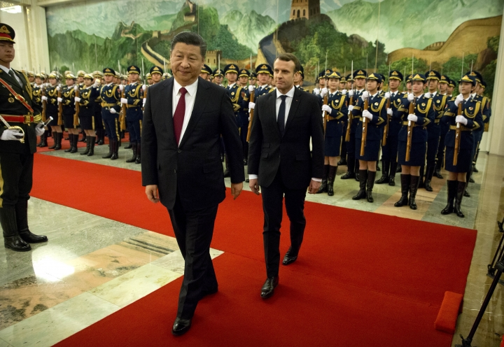 Chinese President Xi Jinping, left, and French President Emmanuel Macron review a Chinese honor guard during a welcome ceremony at the Great Hall of the People in Beijing, Tuesday, Jan. 9, 2018. (AP Photo/Mark Schiefelbein)
