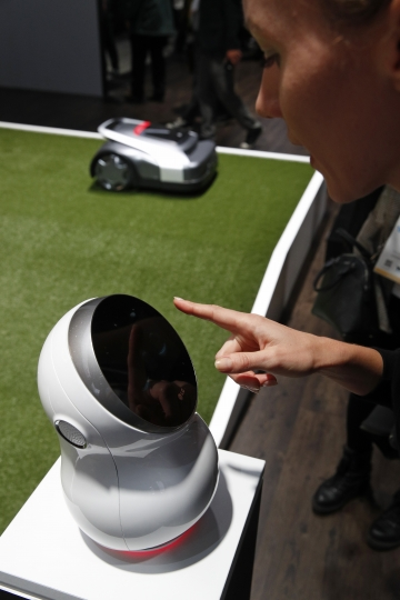 A woman demonstrates a Cloi controlled lawn mower at the LG booth during CES International, Tuesday, Jan. 9, 2018, in Las Vegas. (AP Photo/John Locher)