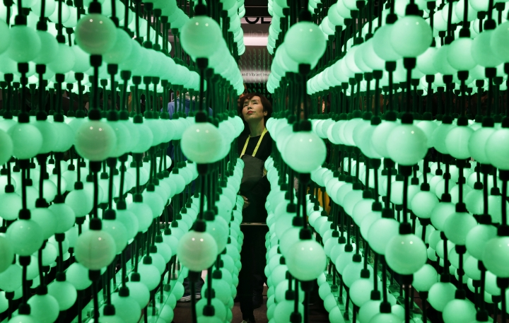 Soyoung Han looks at a display representing LG super UHD TV Nano Cell displays during CES International, Tuesday, Jan. 9, 2018, in Las Vegas. (AP Photo/John Locher)