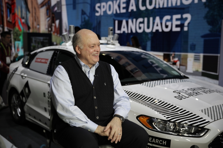 Ford CEO James Hackett smiles while getting ready for an interview next to a self-driving delivery vehicle at CES International, Tuesday, Jan. 9, 2018, in Las Vegas. (AP Photo/Jae C. Hong)
