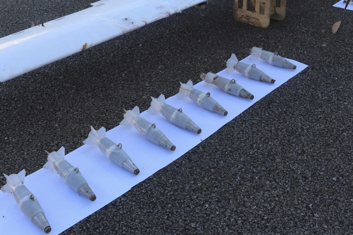In this photo taken from the Russian Defence Ministry Press Service Facebook page on Tuesday, Jan. 9 2018, mortar shells are lined up next to one of the drones that was forced to land after an unsuccessful attack attempt at Hemeimeem air base in Syria. Russia's Defence Ministry said its forces repelled a series of drone attacks on the Hemeimeem air base and a naval facility in Tartus, adding that such attacks would have required assistance from a country possessing satellite navigation technology — a statement that appeared to be aimed at the United States. (Russian Defence Ministry Press Service photo via AP)