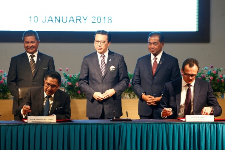Civil Aviation Malaysia's Director General Azharuddin Abdul Rahman and Ocean Infinity's CEO Oliver Plunkett sign documents, witnessed by Malaysia's Transport Minister Liow Tiong Lai, during the MH370 search operations signing ceremony between Malaysia's government and Ocean Infinity, in Putrajaya, Malaysia January 10, 2018. REUTERS/Lai Seng Sin