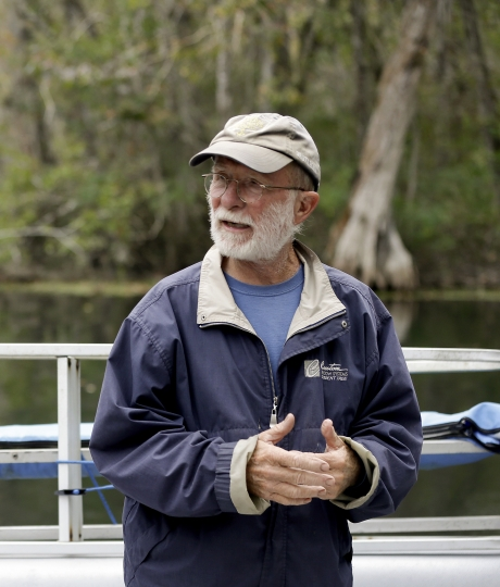 "In this Friday, Nov. 10, 2017 photo Captain Tom O'Lenick keeps a lookout for monkeys and other wildlife as he navigates his boat on the Silver River, in Silver Springs, Fla. The animals' forebears were brought to an island on the Silver River early in the 1930s as a tourist attraction due to the popularity of the Tarzan movies. But there was human error in that plan. ""They didn't know monkeys could swim,"" O'Lenick said. Now there are believed to be about 175 in Silver Springs State Park. (AP Photo/John Raoux)"