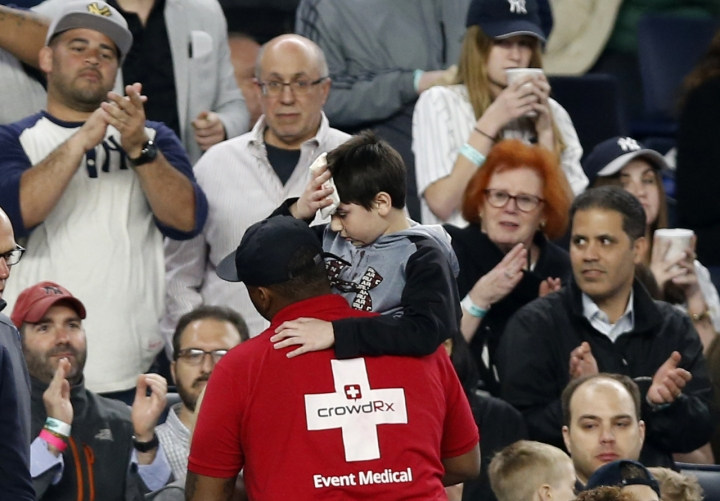 FILE - In this May 24, 2017, file photo, fans applaud as a medical employee carrying an injured youngster from the stands after the boy was hit in the head by a piece of New York Yankees's Chris Carter's bat that split during the seventh inning of a baseball game against the Kansas City Royals at Yankee Stadium in New York. The Yankees are expanding netting to protect seats behind each dugout and for five sections past down both foul lines, a decision announced after several fans were injured last year.(AP Photo/Kathy Willens, File)