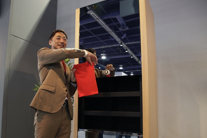 Seven Dreamers CEO Shin Sakane demonstrates use of the Laundroid, a laundry folding machine, at CES International, Wednesday, Jan. 10, 2018, in Las Vegas. (AP Photo/Jae C. Hong)